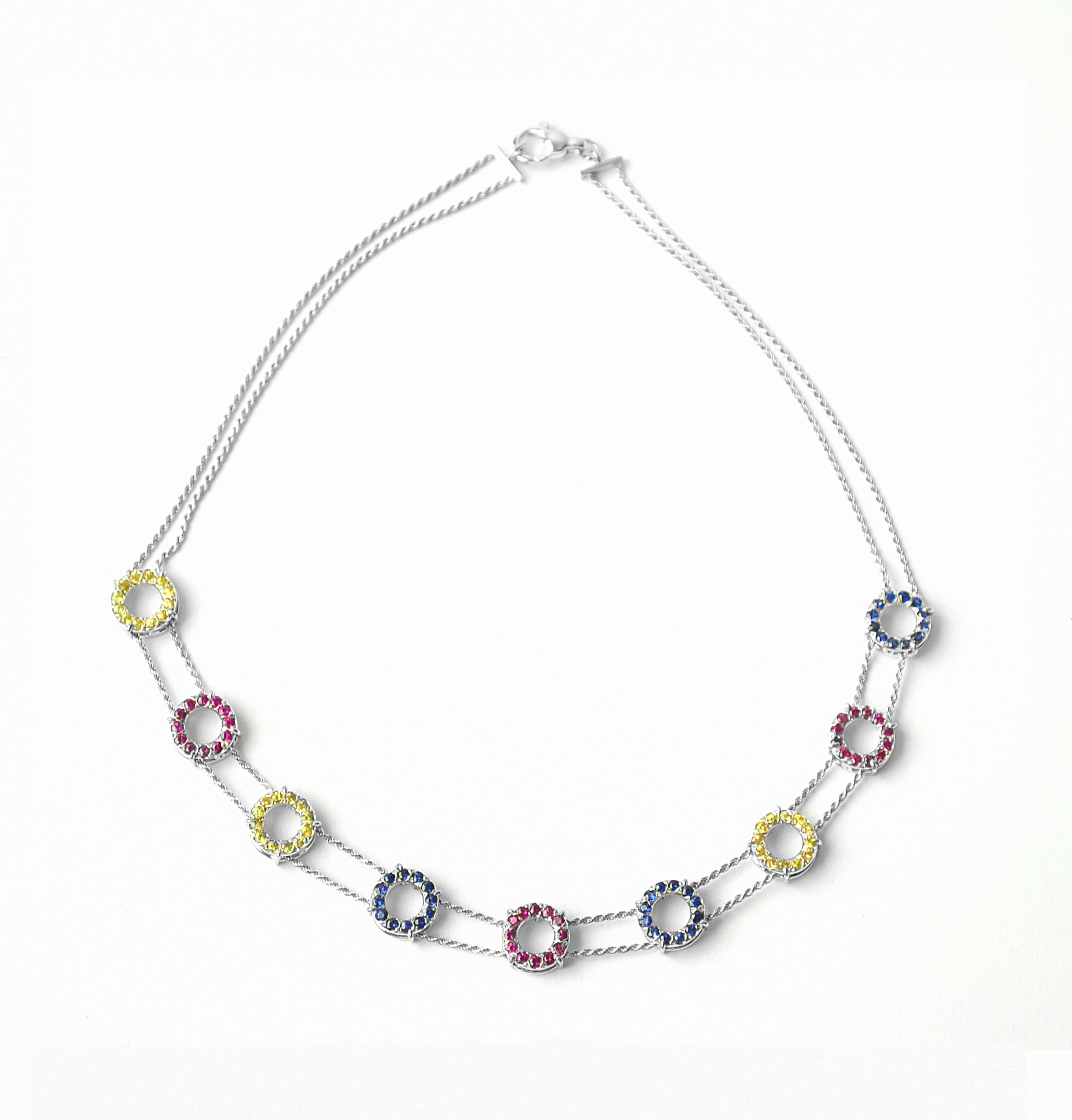 Necklace in white Gold chains and circle elements with yellow & blue Sapphires and Ruby ​​sapphires set.